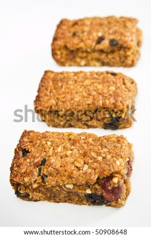 Three pieces of fresh homemade cherry and raisin flapjack, in a row on a white table cloth with short depth of field. - stock photo