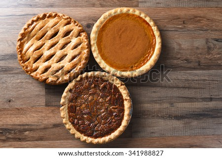 Three pies for Thanksgiving on a wood surface. The desserts include apple, pumpkin and pecan pies - all traditional treats for the American Holiday. - stock photo