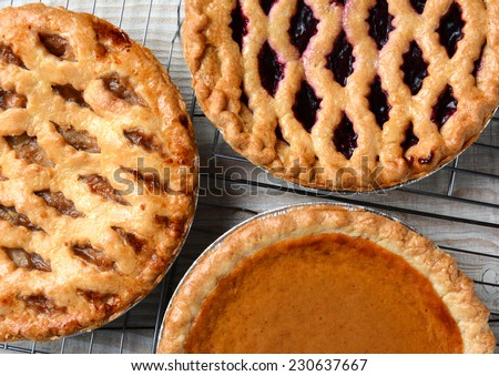 Three pies on cooling racks. High angle closeup shot of fresh baked apple, cherry and pumpkin pastries on wire racks on a rustic wood kitchen table. Horizontal format. - stock photo