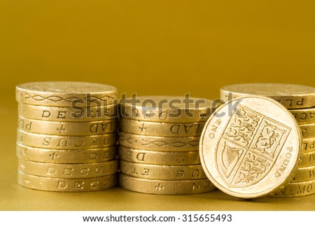 Three piles of English pound coins set against a golden background - stock photo