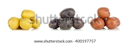 Three piles of yellow, purple and red fresh little potatoes over a white background - stock photo