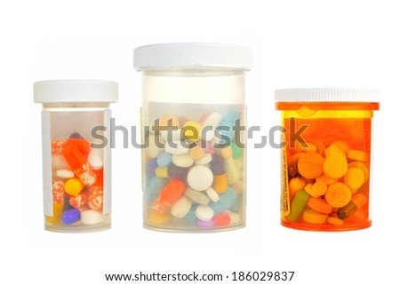 Three pill bottles filled with assorted medications isolated on white                       - stock photo