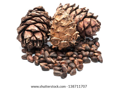 Three pine cones and a handful of nuts isolated on white. - stock photo