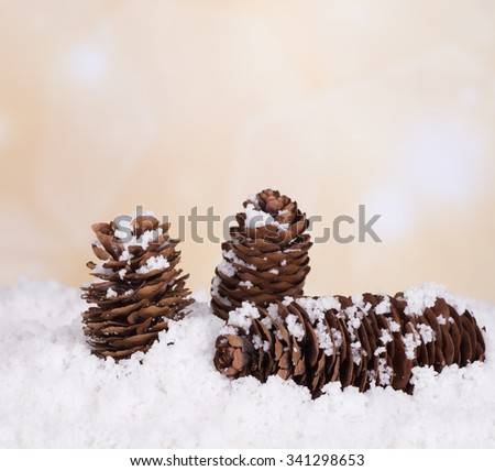 Three pine cones in snow with holiday background - stock photo