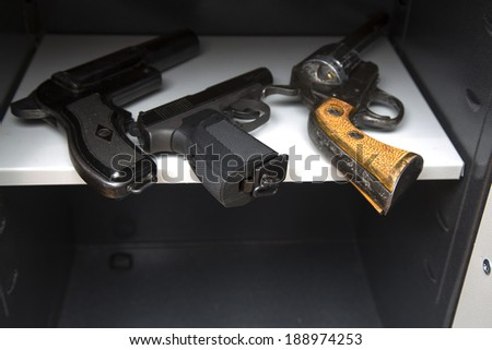 three pistols in the open safe - stock photo