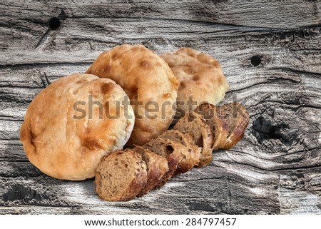 Three Pita Bread loafs and Baguette Integral Brown Bread slices, on old, weathered, Wooden Table surface.  - stock photo