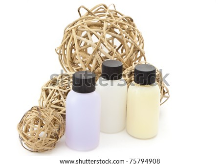 Three plastic bottles of colored liquid framed by wicker balls - stock photo