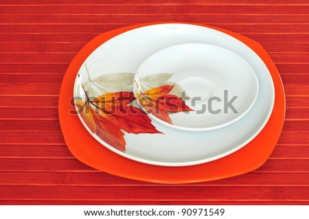 Three plates on red wooden background - stock photo