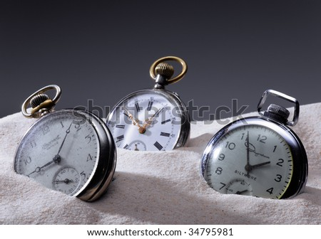 Three pocket watches in sand - stock photo