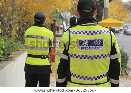 Three policemen seen from the backside at a street in Seoul, South Korea - stock photo