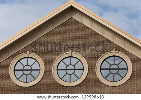 Three portal style windows on brick wall with cloudy blue sky above a copper roof building. - stock photo