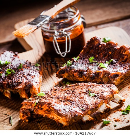 Three portions of barbecued ribs in a spicy marinade seasoned with pepper and fresh herbs being prepared in a country kitchen with a jar of basting sauce - stock photo