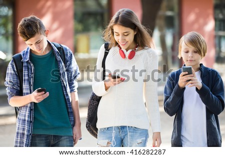 Three positive american teenagers with smartphones in autumn day outdoors  - stock photo