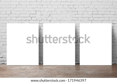 three  poster standing next to a brick wall - stock photo