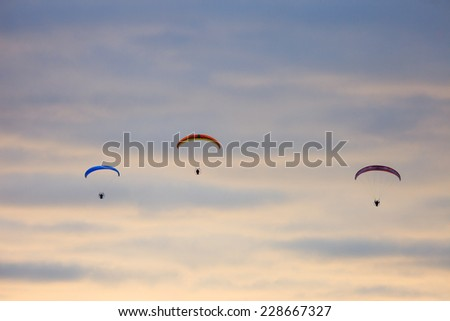 Three Powered Parachutes on Morning Sky - stock photo
