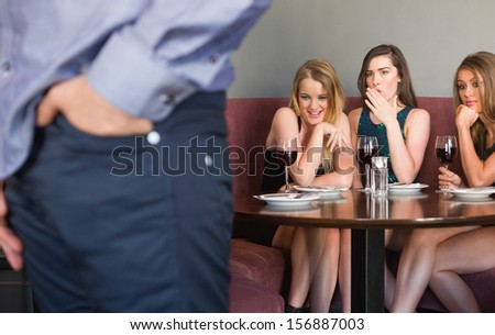 Three pretty friends checking out mans rear in a nightclub - stock photo