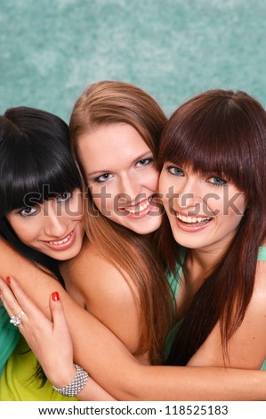 three pretty girls in green dresses on a green - stock photo
