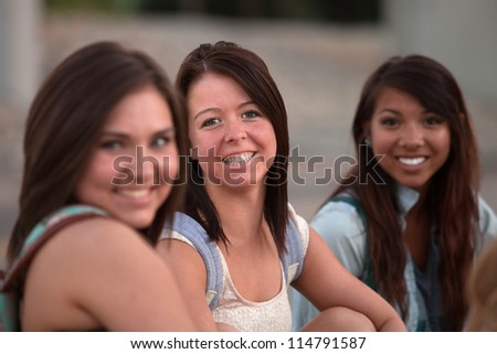 Three pretty teenage students smiling and sitting together - stock photo