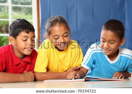 Three primary school friends reading and learning - stock photo