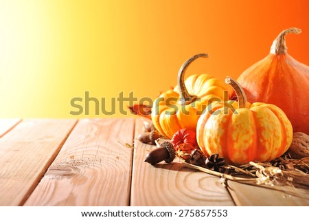 three pumpkins on old weathered wood grain with brown background with light from the side - stock photo