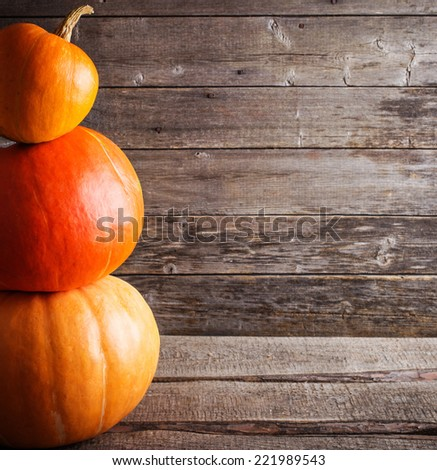 three pumpkins on wooden background - stock photo