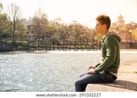 Three-quarter length of contemplative light brown haired teenage boy wearing green hooded-shirt and denim jeans sitting on wall beside picturesque river in Turin, Italy - stock photo