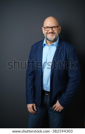 Three Quarter Length Portrait of Confident Mature Man with Facial Hair and Eyeglasses Wearing Business Casual Clothing and Standing in Studio with Dark Gray Background and Copy Space - stock photo