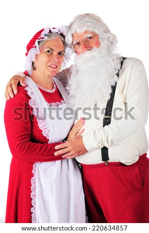 Three-quarter length portrait of Mr. and Mrs. Santa in their at-home attire.  On a white background. - stock photo