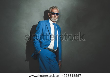 Three-Quarter Shot of a Middle Aged Businessman Wearing Blue Suit with Sunglasses, Leaning Against Gray Wall with Copy Space. - stock photo