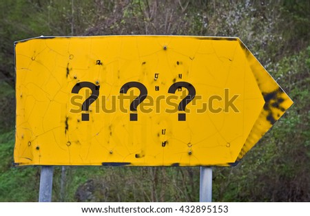 Three question marks written on a yellow road sign - stock photo