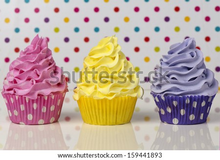 Three rainbow cupcakes on dotted background - stock photo