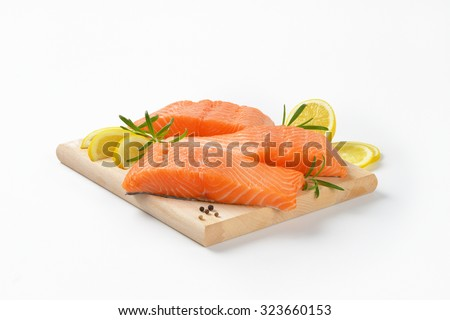 three raw salmon fillets on wooden cutting board - stock photo