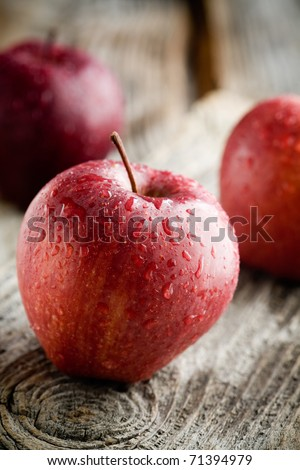 Three red apples on wooden table, selective focus - stock photo
