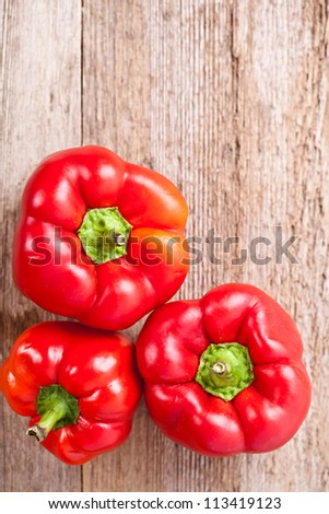 three red bell peppers on rustic wooden table - stock photo