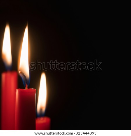 Three red candles burning in front of black background, copy space on the right side ot the image - stock photo