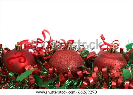 Three red Christmas baubles on green tinsel isolated on white background with copy space. - stock photo