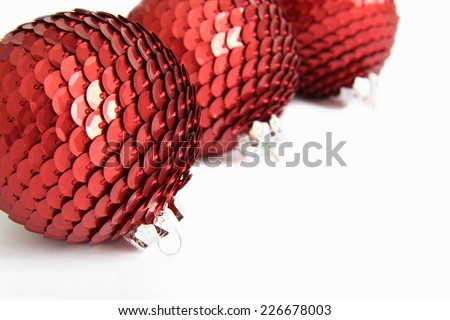 Three red Christmas sequin baubles on white. - stock photo