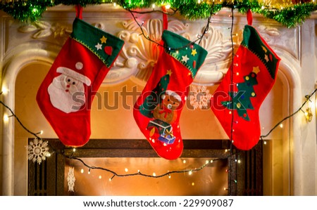 Three red christmas stockings hanging on decorated fireplace - stock photo