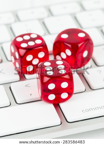 Three red dice on keyboard, online casino concept - stock photo