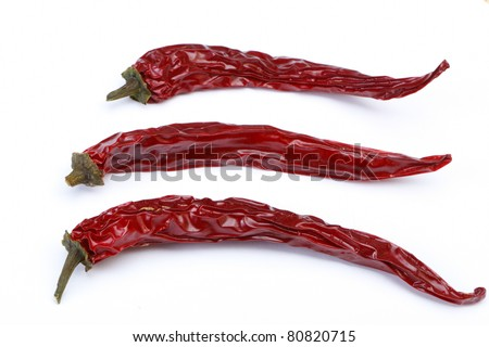 Three red dried chilis on white background - stock photo