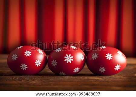 Three red Easter eggs on wooden table and red curtain background - stock photo