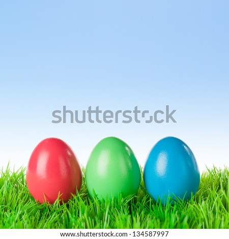 Three red green blue colored easter eggs on a meadow over a bright clear sky. - stock photo