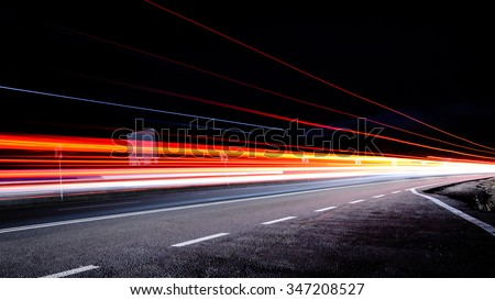 Three red lines / red light trails at night on the road - stock photo