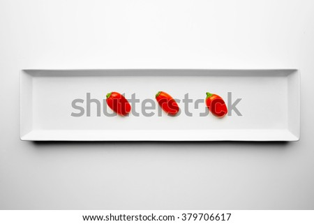 Three red peppers isolated in center of rectangular ceramic plate on white background - stock photo