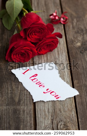 three red roses on wooden rustic table and hand written words I love you - stock photo