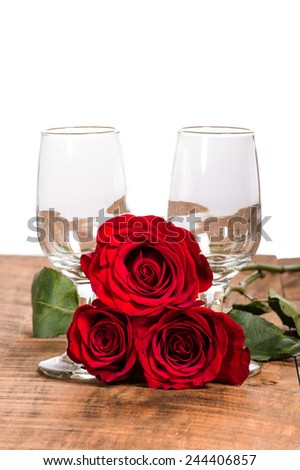 Three red roses with empty wine glasses - stock photo