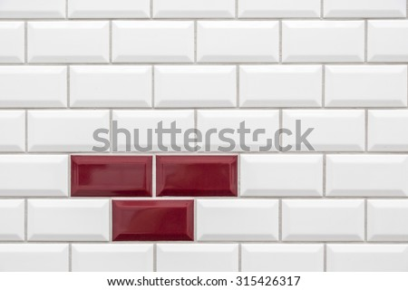 Three red tiles in many white tiles - stock photo
