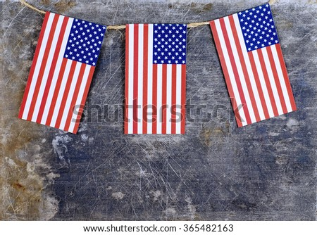 Three red, white and blue USA flags suspended from a twine rope in front of a grungy, steel background for any patriotic day in the United States.  Thematic message across bottom of horizontal image. - stock photo