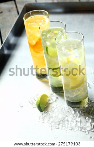 Three refreshing tangy citrus summer cocktails served in tall glasses flavoured with lemon, lime and orange and chilled on ice, high angle view in a receding row - stock photo
