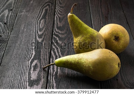 Three ripe juicy pears conference on a dark wooden table - stock photo